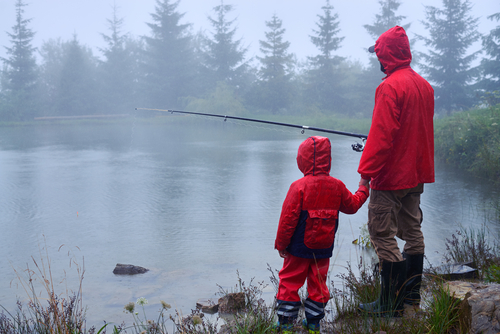 father and son fishing together in the rain