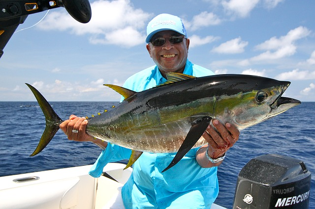 man wearing polarized sunglasses holding a tuna on a boat