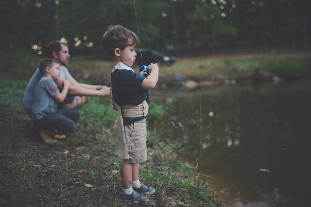 child fishing in pond with father and sibbling