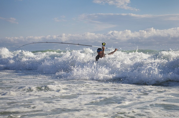 man casting surf rod and reel combo in the waves